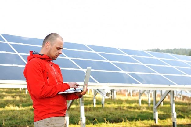 Мужской инженер, используя ноутбук, солнечные панели в фоновом режиме
