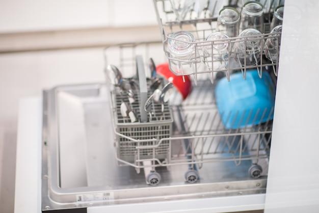 きれいなガラスと食器を入れた食器洗い機を開く
