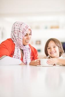 現代の新しい白い家で幸せな母と息子