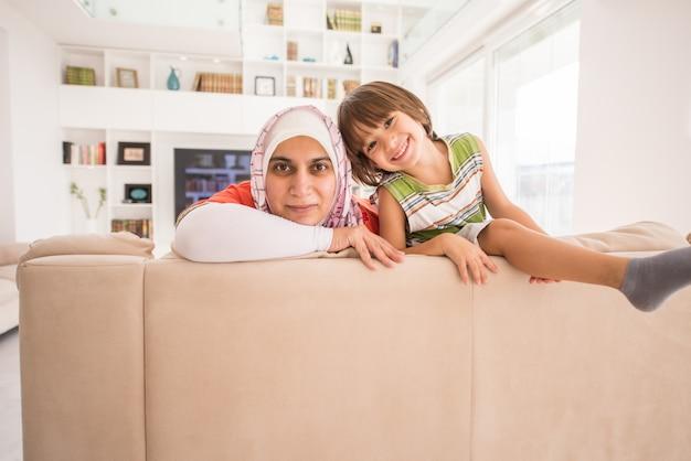 リビングルームに家で小さなかわい子とイスラム教徒の伝統的な母親