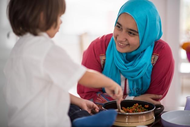イスラム教徒のアラビア語の若い母親と小さなかわいい息子が料理を作り、キッチンで楽しい