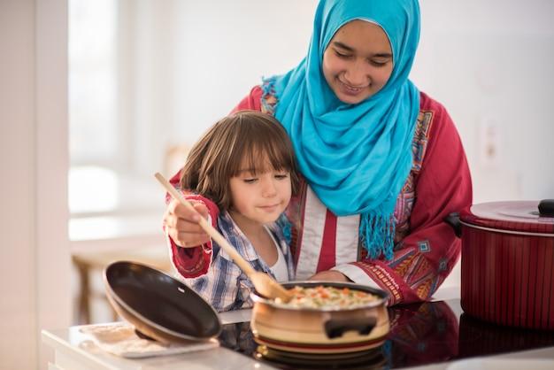 キッチンに小さな子供を持つアラビア語の若い女性