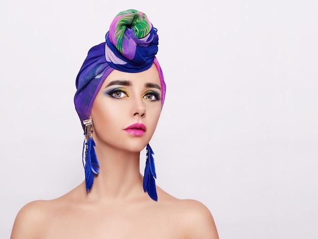 Портрет молодой женщины с ярким макияжем и модный платок на светлой стене.