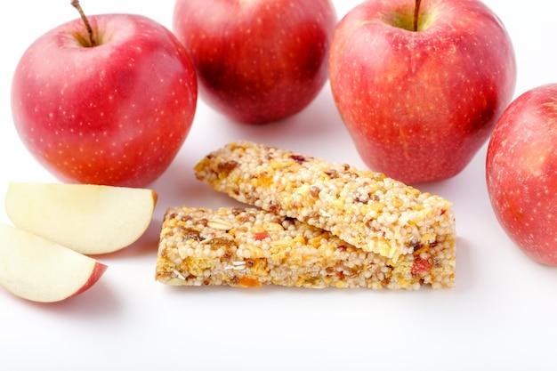 Коричневые батончики с гранолой и красные яблоки