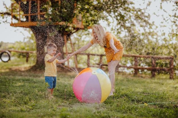 黄色の夏のドレスと木の家の近くのしぶきのボールで遊ぶ幼い息子の若いかなり裸足の母