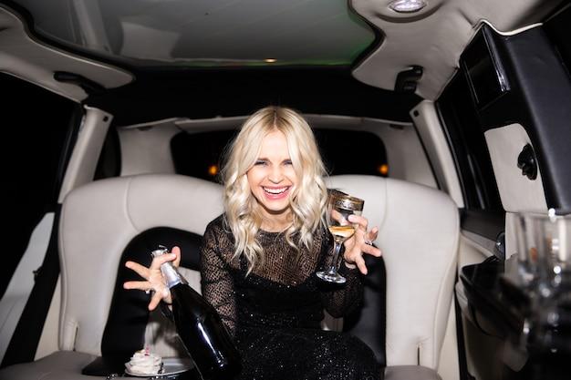 シャンパンとリムジンでケーキとパーティーを持つ若いブロンドの女性