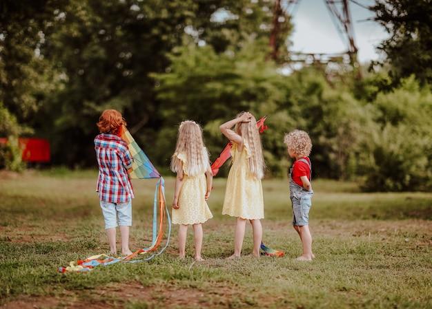緑の空き地で明るい凧で遊ぶ子供たち