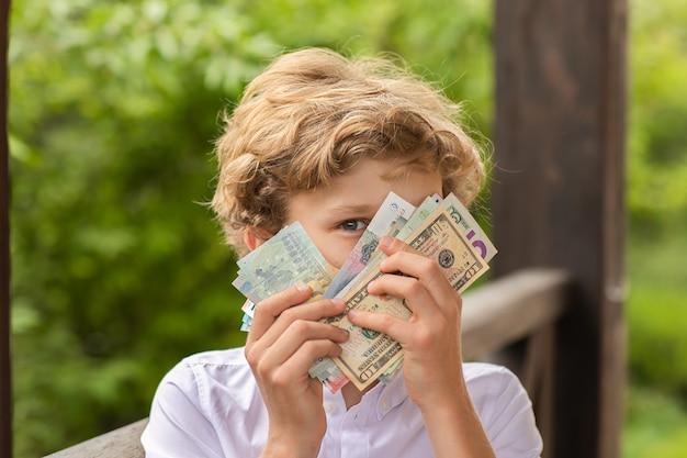Подросток мальчик держит деньги на руках