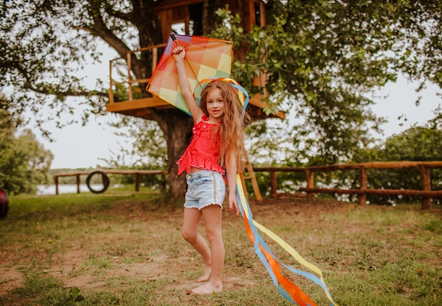Маленькая девочка, играя с красочными кайт