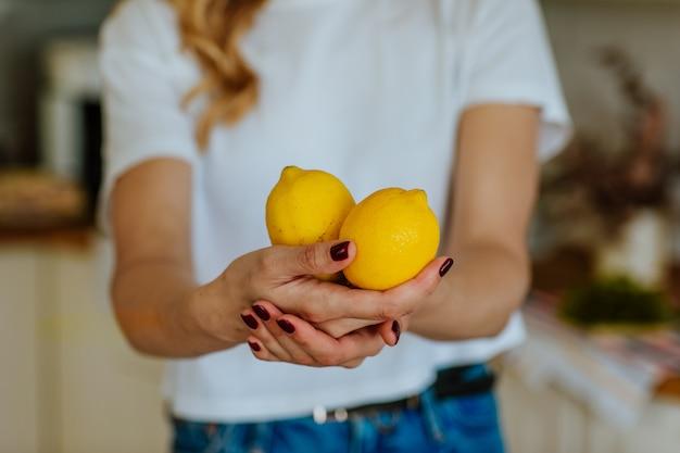 Молодая женщина с двумя желтыми лимонами на белой кухне