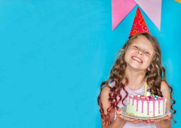 青の背景にケーキを保持している若い祝っている女の子。コピースペース
