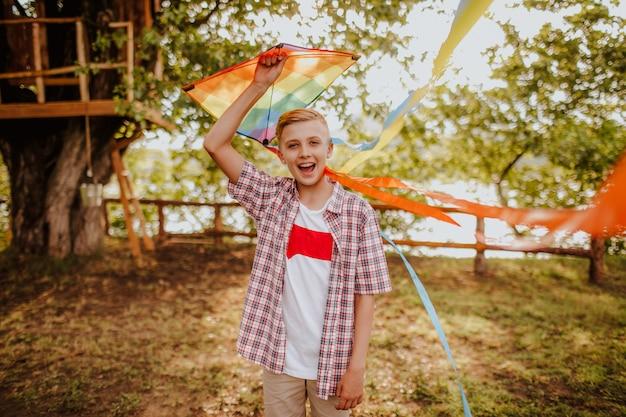 Белокурый мальчик-подросток с красочным воздушным змеем
