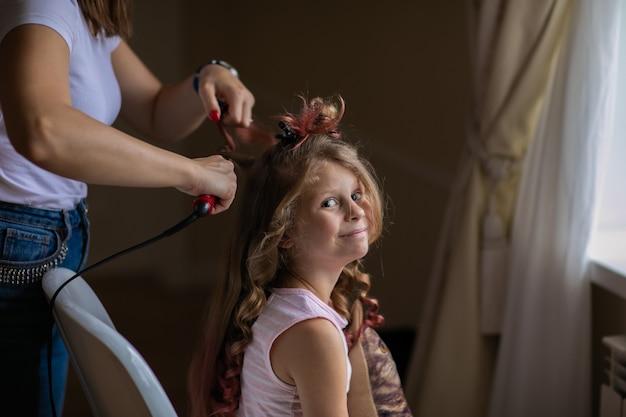 屋内で長い髪のかわいい少女に巻き毛のアイロンで美容を作る女性。