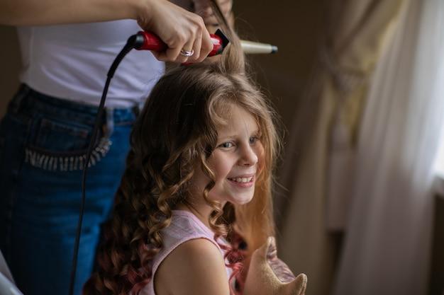 屋内で長い髪のかわいい少女に巻き毛のアイロンで美容を作る女性。カーリースタイル。