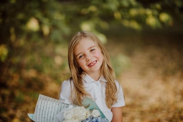 Портрет школьницы в белой рубашке с букетом цветов и улыбкой