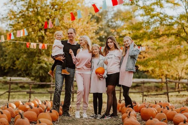 Большая семья проводит время на тыквенной ферме. время падения