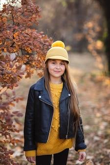 Молодая девушка с длинными светлыми волосами в желтый свитер, шляпа и кожаная куртка, позирует в осенний парк. копировать пространство