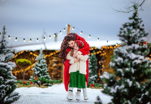 若いかなり長い髪の女の子とオープンスケートリンクでスケートの美しいブルネットの女性。クリスマスの背景。