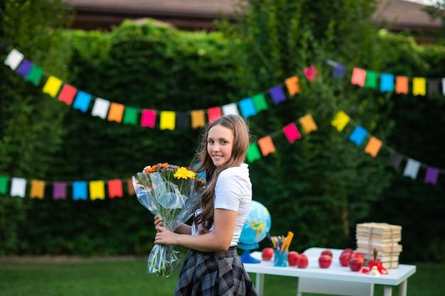 花の花束とポーズの制服で長い髪の若い十代の少女