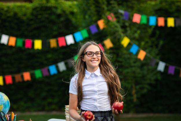 赤いリンゴを保持している白いシャツでメガネの若い十代の少女