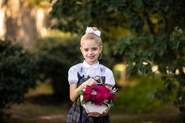 花束の花を保持している制服の少女の肖像画
