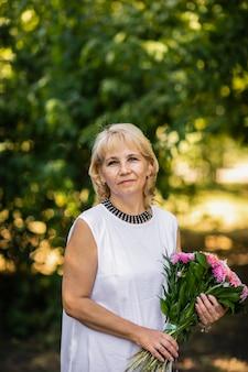大人の先生が校庭で花の花束でポーズ