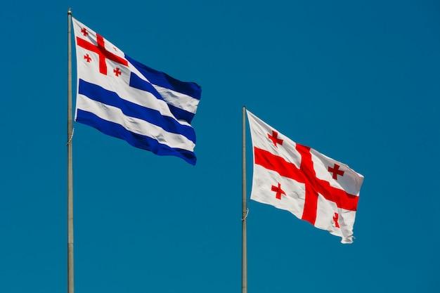 Большой развевающийся флаг автономной республики аджария и флаг грузии, также известный как пятикрестный флаг на фоне голубого неба, батуми, аджария, грузия