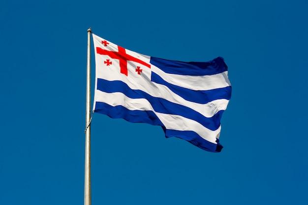 Большой развевающийся флаг автономной республики аджария на фоне голубого неба, батуми, аджария, грузия
