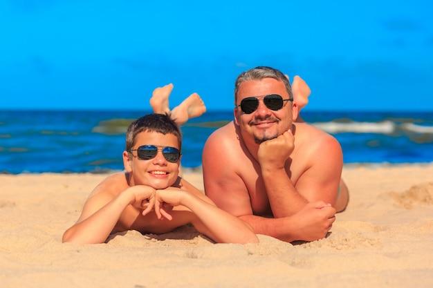 Счастливый молодой мальчик и мужчина на берегу моря
