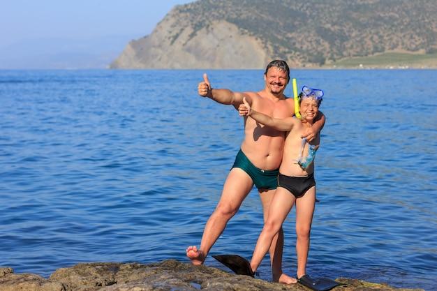 Счастливый отец и сын на берегу моря