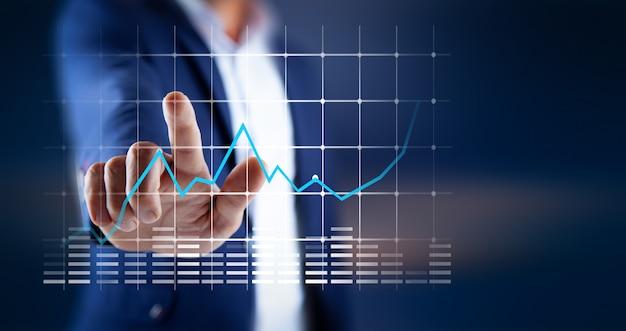 画面のビジネスグラフに触れる男