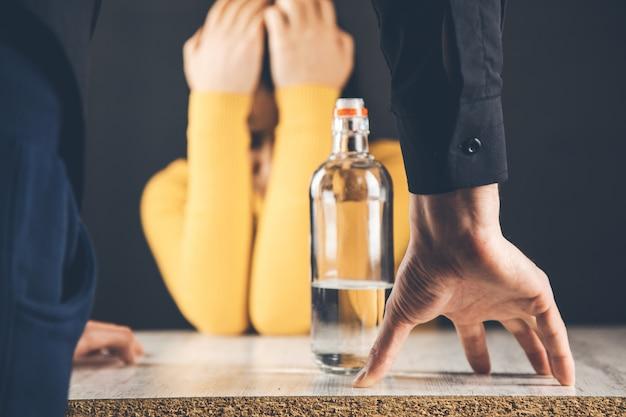 悲しい女と男の手アルコール