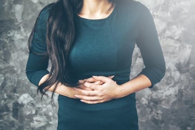 胃の中で悲しい女性の手