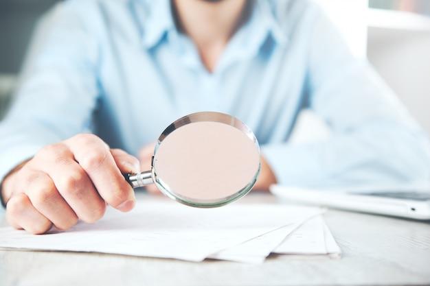机の上の書類と男の手の拡大鏡