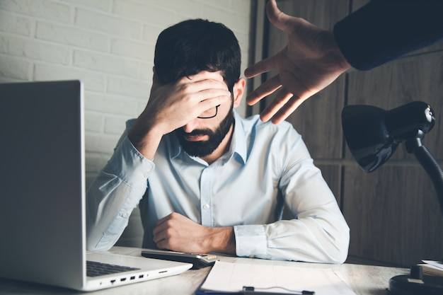 オフィスの机の上の悲しい男と怒っている上司