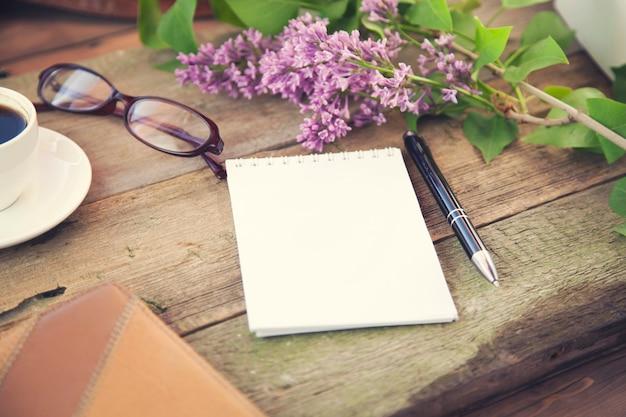 コーヒー、ペン、メモ帳、メガネ、花
