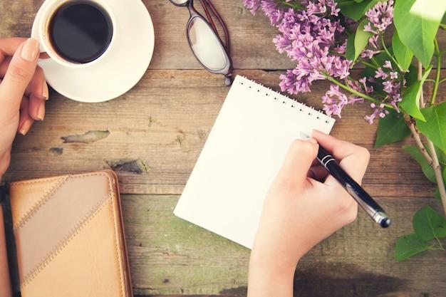 女性の手ペンとコーヒー