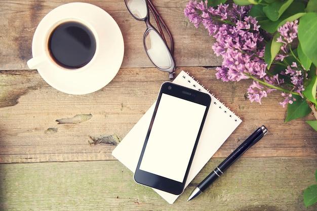 テーブルの上のメモ帳、ペン、コーヒー、グラス、花の電話