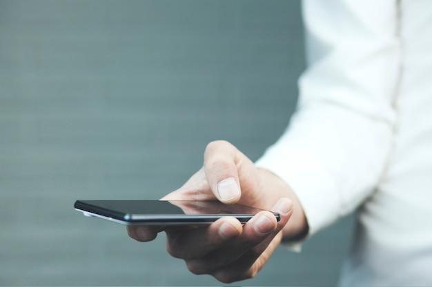 Мужской рукой, придерживая пустой мобильный смартфон