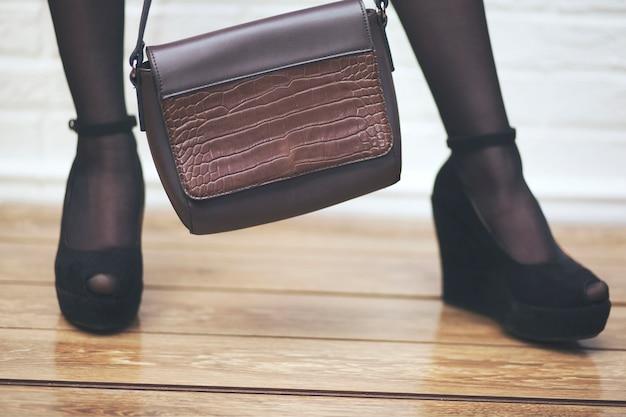 ハンドバッグの女性のセクシーな脚