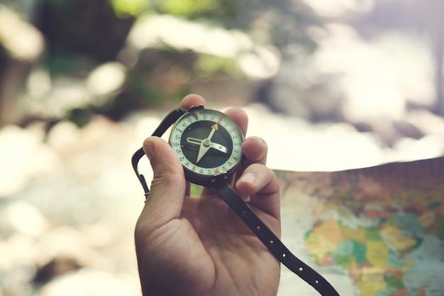 男の手のコンパスと自然の地図