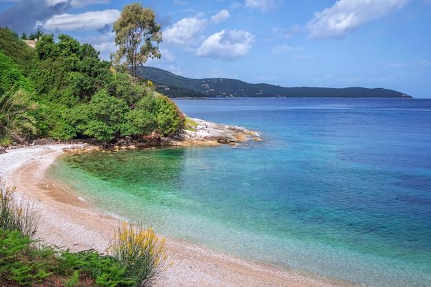 Красивый пейзаж - морская лагуна с бирюзовой водой, камни и камни, оливковое дерево, растущее на холме, голубое небо с облаками и горы на горизонте. остров корфу, греция.
