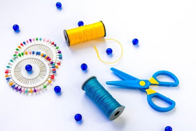 青と黄色の糸、はさみ、ガラスベッド、白地にカラフルなピンのスプールを縫製