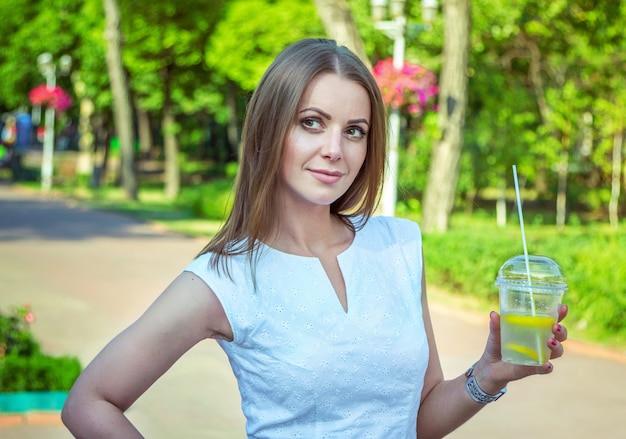 Красивая молодая улыбающаяся женщина, одетая в элегантное белое платье, стоит в парке, держит в стакане лимонадный коктейль, освежается в жаркий летний день