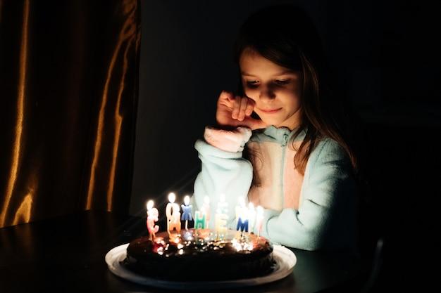 かわいい女の子が彼女の誕生日ケーキにろうそくを吹く前に願い事をして