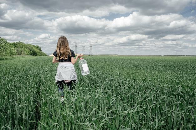 Маленькая русская девушка с бутылкой для воды гуляя через поле молодой зеленой пшеницы. летний пейзаж, вид со спины.