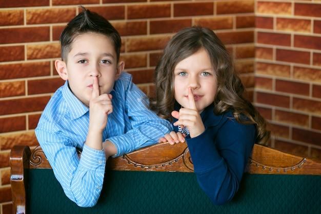 陽気な兄と妹のイメージは、唇に指を合わせます。面白い秘密の明るい服