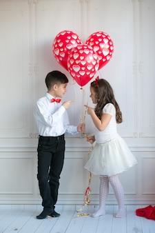 小さな子供たちを保持し、ハートの風船を拾います。バレンタインデーと愛の概念