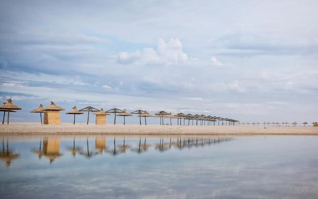 Соломенные зонтики стоят в ряд на песчаном морском побережье и отражаются в голубой воде.