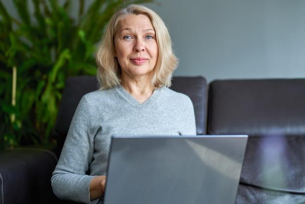 オフィスのソファーに座ってオンライン作業実業家。